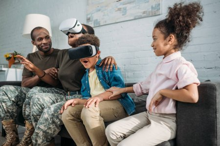 African american female and male soldiers and their children using Virtual reality headsets