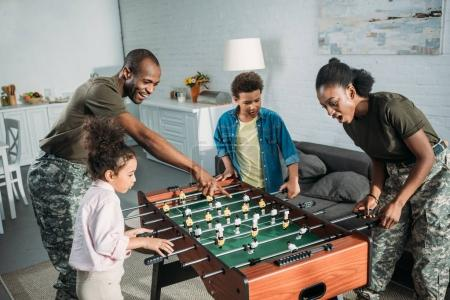 Woman and man in army uniform and cheerful kids playing table football