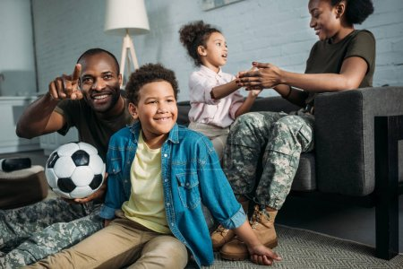 African american female and male soldiers playing with their children at home