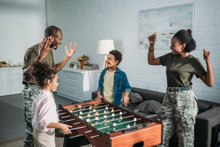 Army soldiers with happy kids playing table football