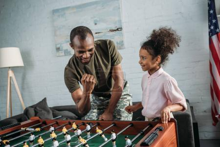 Happy family of soldier father and african american daughter playing table football