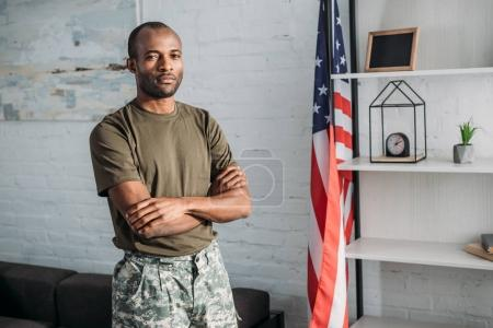 Confident man in camouflage clothes standing in room with flag
