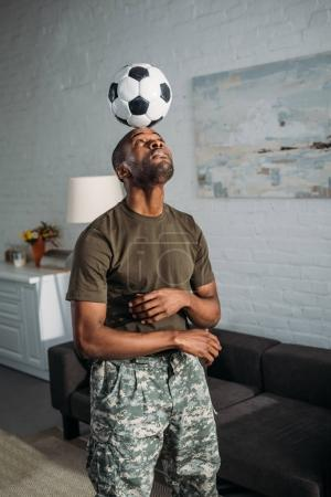 African american soldier playing with football ball on head