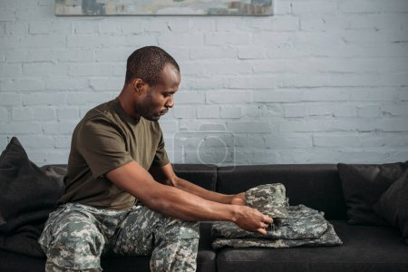African american male soldier folding camouflage clothes on sofa