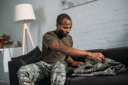 Male army soldier folding camouflage clothes on sofa
