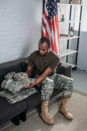 Handsome male soldier folding camouflage clothes on sofa