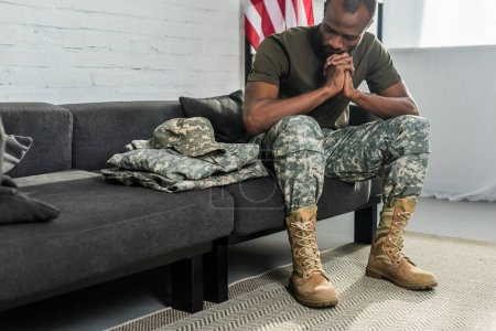 Thoughtful soldier sitting on sofa and looking at his camouflage clothes