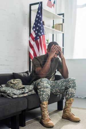Upset army soldier sitting on sofa with camouflage clothes