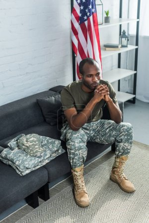 Thoughtful soldier sitting on sofa with camouflage clothes
