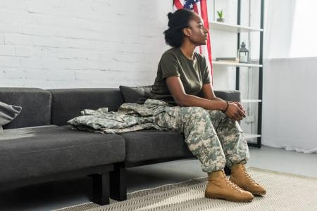 Young female soldier in camouflage clothes waiting on sofa in room