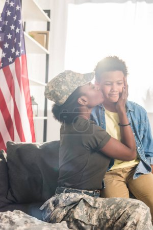 Female soldier in camouflage clothes kissing her son
