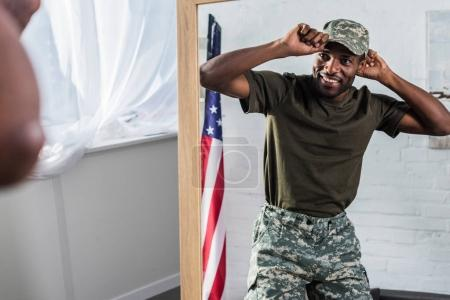 Smiling african american soldier in camouflage clothes posing by the mirror