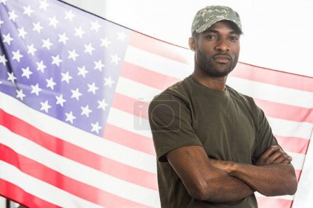 Handsome african american soldier in camouflage clothes in front of us flag
