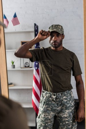 Handsome african american soldier in camouflage clothes posing by the mirror