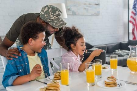 Father in army uniform and african american kids eating breakfast with pancakes