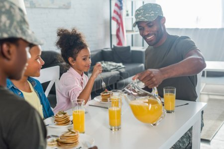 Happy family with children and parents in army clothes enjoying breakfast