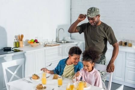 Army soldier father looking at happy kids enjoying meal in kitchen