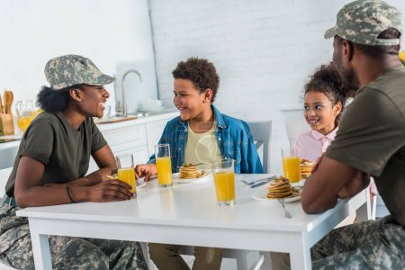 Parents in camouflage clothes with children enjoying meal in kitchen