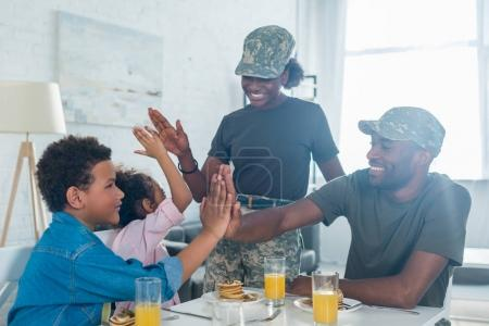 Parents in camouflage clothes giving five to their children by kitchen table