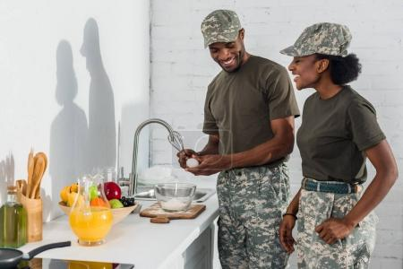 Couple of soldiers cooking together at home kitchen
