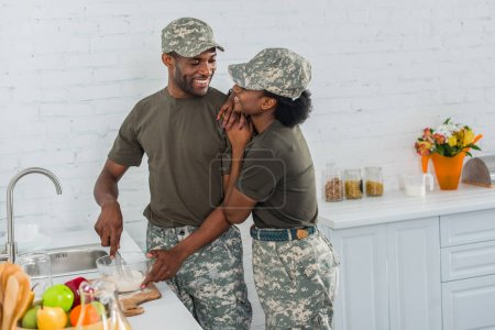 Woman and man in army uniform hugging in kitchen