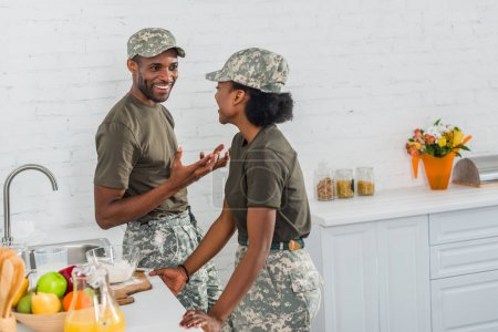 Couple of african american army soldiers talking in kitchen at home