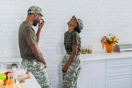 Couple of african american soldiers laughing together in kitchen