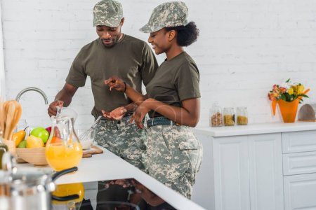 African american female soldier with man cooking together at home kitchen