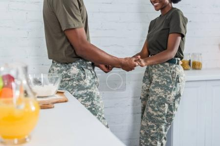 Cropped view of african american man and woman soldiers holding hands at home kitchen