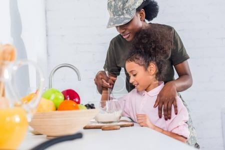 African american soldier with little daughter cooking together at home kitchen