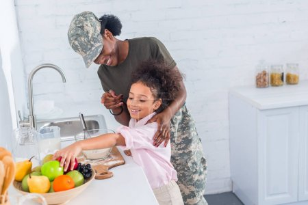 Mother soldier and african american child cooking together