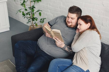 boyfriend and girlfriend reading book together on sofa in living room