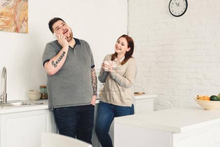 Photo pour Heureux petit ami parler de smartphone et sa petite amie tenant la tasse de café dans la cuisine - image libre de droit