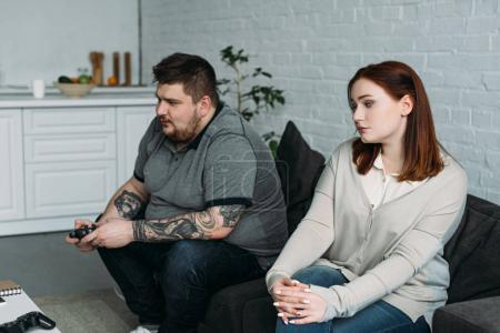 Photo for Worried girlfriend sitting on sofa while boyfriend playing video game at home - Royalty Free Image