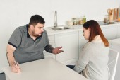 overweight boyfriend quarreling with girlfriend and holding smartphone in kitchen
