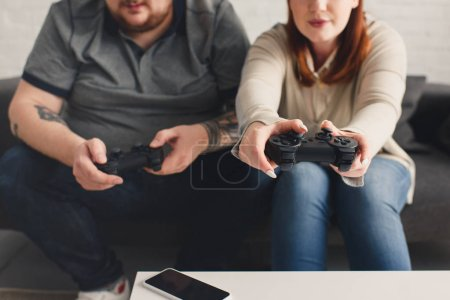 Photo for Cropped image of boyfriend and girlfriend playing video game at home - Royalty Free Image