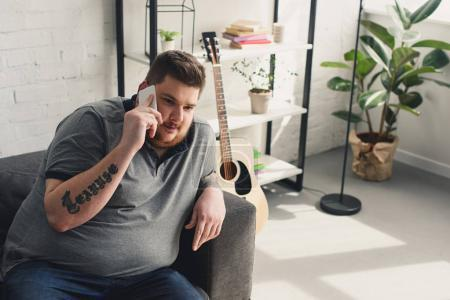 overweight man talking by smartphone on sofa at home