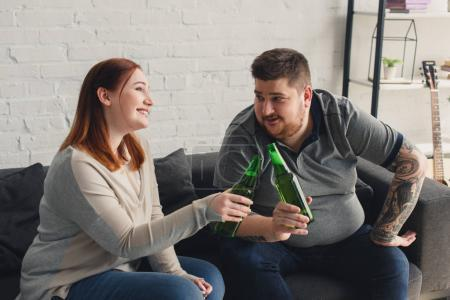 smiling overweight boyfriend and girlfriend clinking with bottles of beer