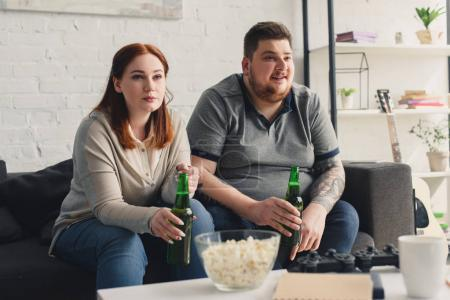 Overweight couple watching tv