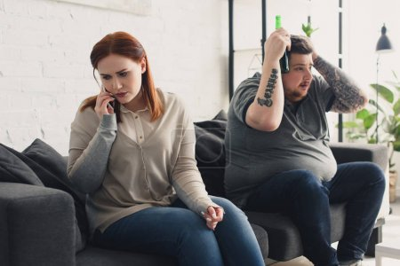 girlfriend talking by smartphone and boyfriend watching tv with beer at home