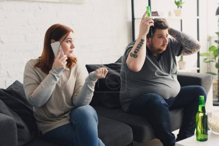 girlfriend talking by smartphone and looking at boyfriend watching tv with beer at home