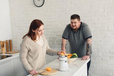 Photo pour Petit ami en surpoids et petite amie préparant du jus d'orange à la cuisine - image libre de droit