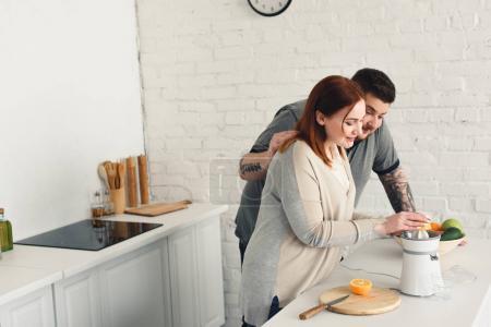 Photo pour Copain copine étreignant alors qu'elle faire du jus à la cuisine en surpoids - image libre de droit