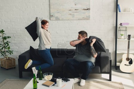 boyfriend and girlfriend fighting with pillows in living room