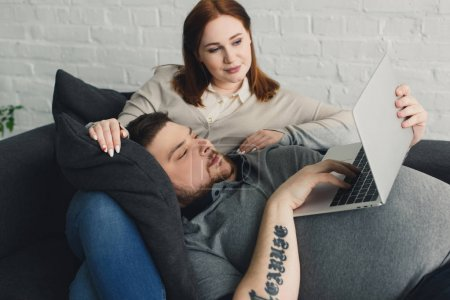 Overweight couple using laptop