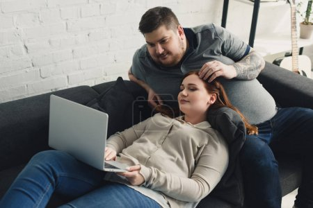 boyfriend touching girlfriend hair and looking at laptop at home