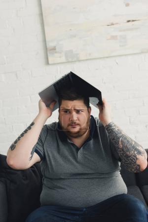 Photo pour Bel homme tenant portable sur la tête et à la recherche de suite à domicile - image libre de droit