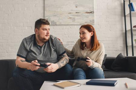 smiling girlfriend palming boyfriend while playing video game at home