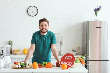Photo for Smiling handsome vegan man standing near kitchen counter with vegetables and no meat sign - Royalty Free Image