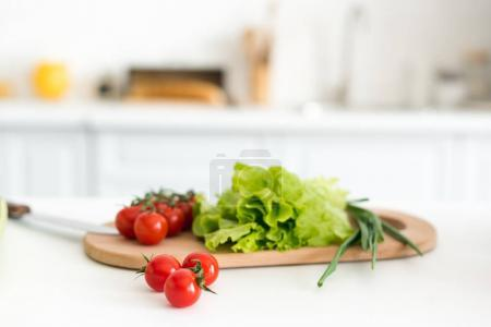 Photo for Cherry tomatoes and salad leaves on cutting board in kitchen - Royalty Free Image